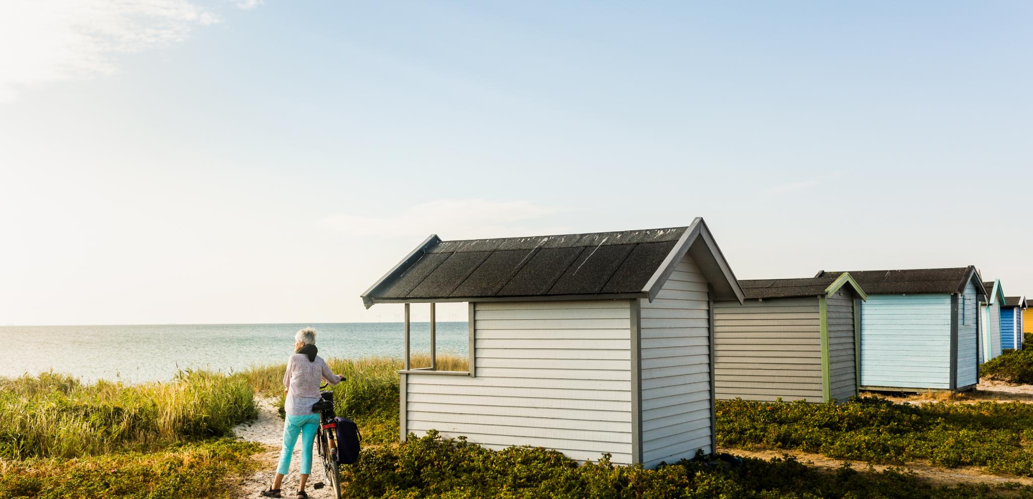 Bathing huts facing a beach. A woman with her bike stands nex to it and looking out.