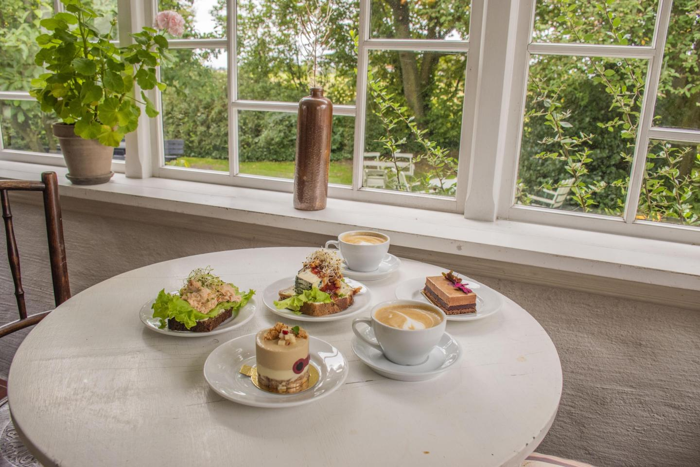 A table with sandwiches, pastries and coffee overlooking the garden