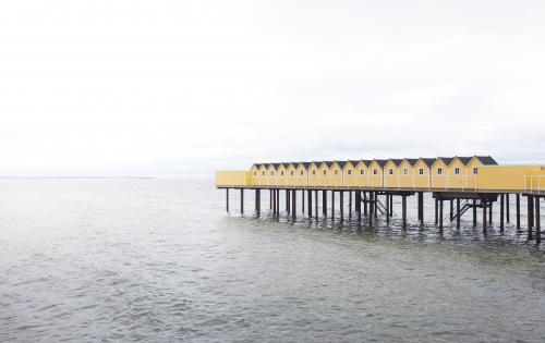 Open-air bathhouse held up by pier stilts in the sea