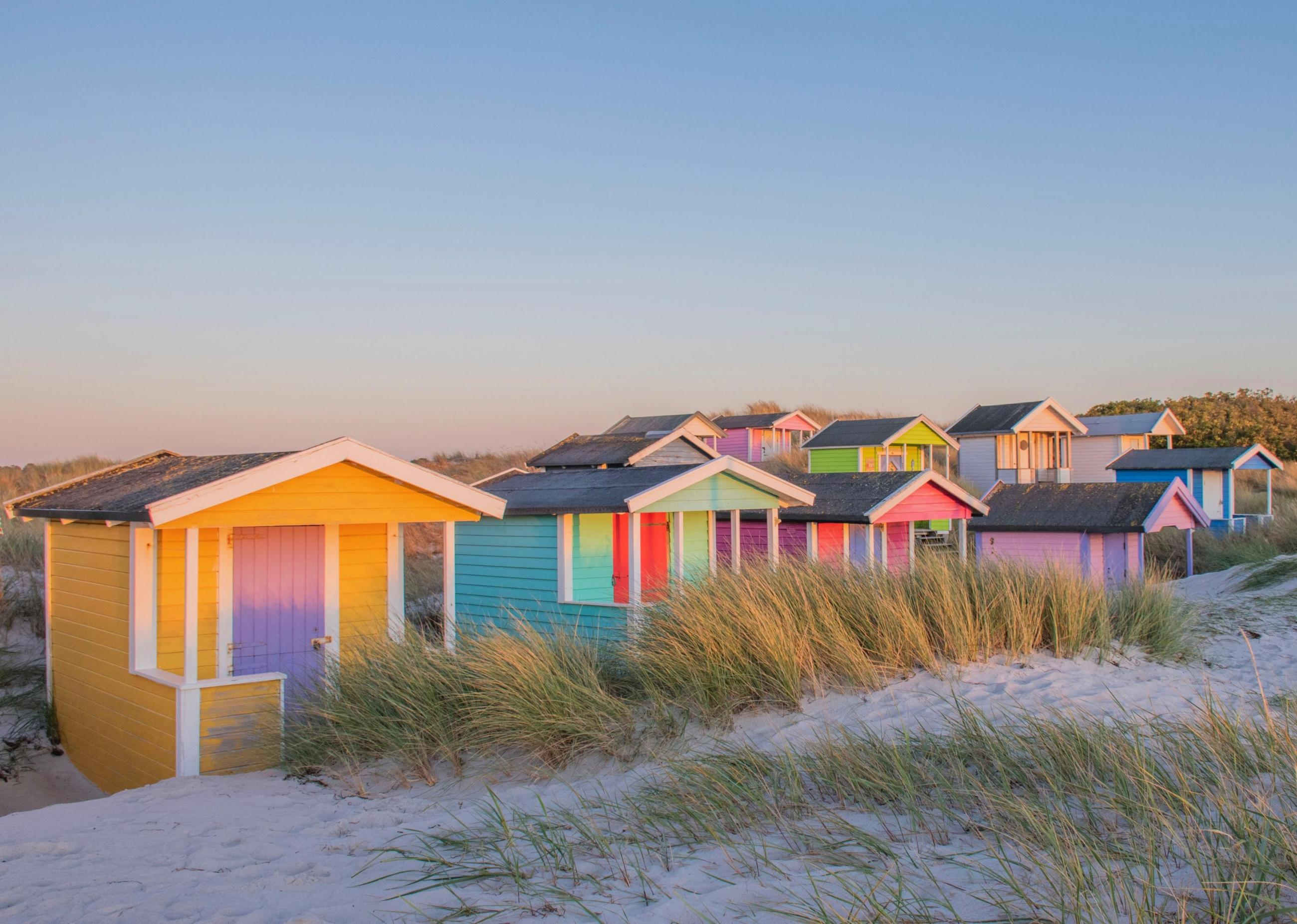 Colorful bathing huts on a white beach under a clear bluse sky.