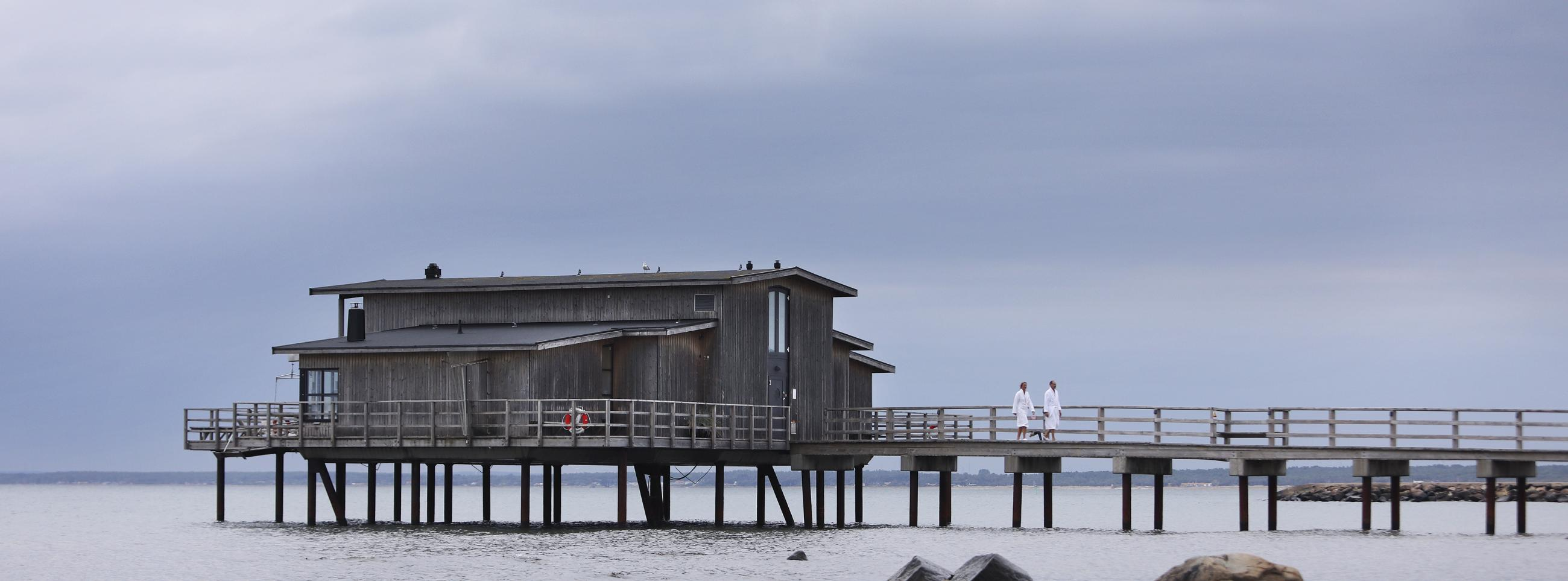 Land view of open-air bathhouse held up by pier stilts in the sea