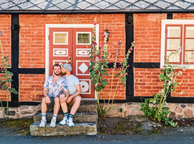 Couple of men sitting in a staircase souronded by flowers in Kivik